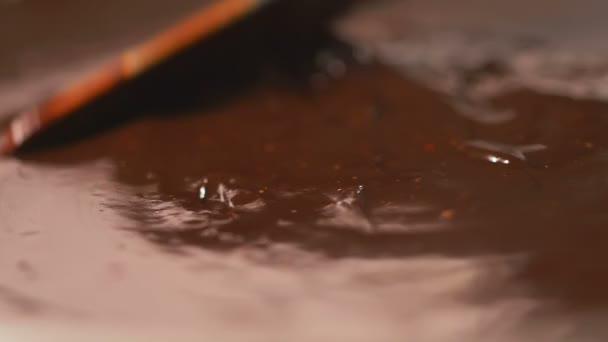 köstliche geschmolzene Schokolade in Zeitlupe mit einem Messer mischen
