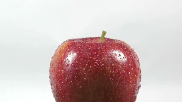 Close-up of a delicious red apple sprinkled with water rotating
