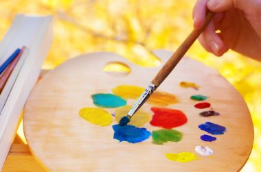 The artist mixes paint on the palette