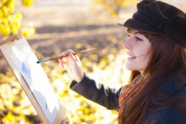 The girl draws on nature autumn