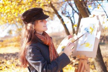 The girl draws on nature autumn