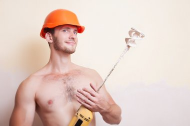 Man in helmet with a mixer for plastering