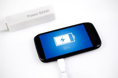 Smart phone charging with power bank on white background