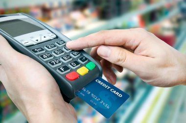 Hand with credit card swipe through terminal for sale in superma