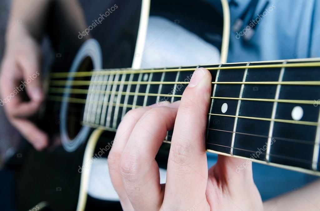 Close Up Of Playing Guitar Musician Holding A Chord Stock Photo