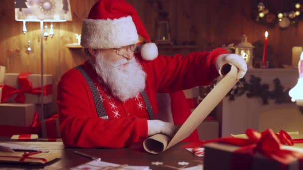 Glücklicher Weihnachtsmann mit Pergament-Wunschliste am heimischen Tisch.