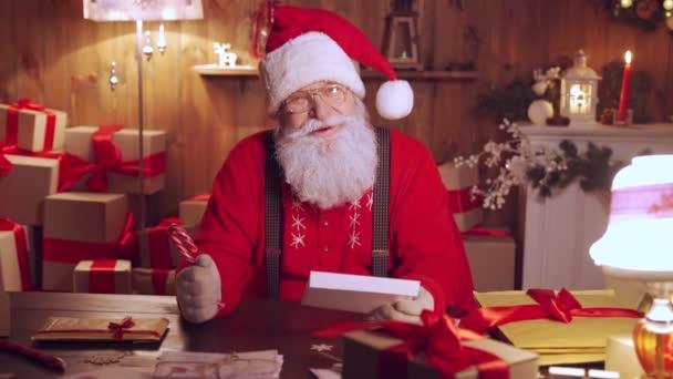 Glücklicher Weihnachtsmann im Gespräch mit der Kamera am heimischen Tisch mit Geschenken.