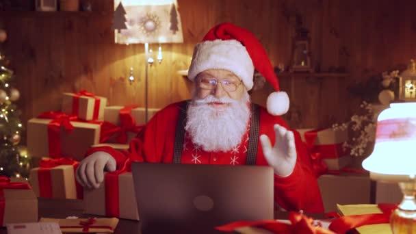 Weihnachtsmann-Video ruft Kind am Laptop an und bereitet Geschenk am heimischen Tisch vor.