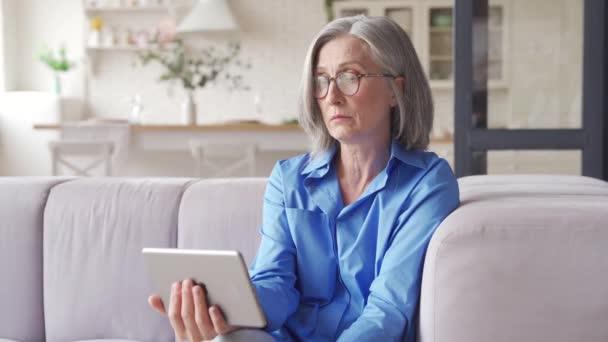 Seniorin mit digitalem Tablet-Video ruft Arzt zu Hause an.