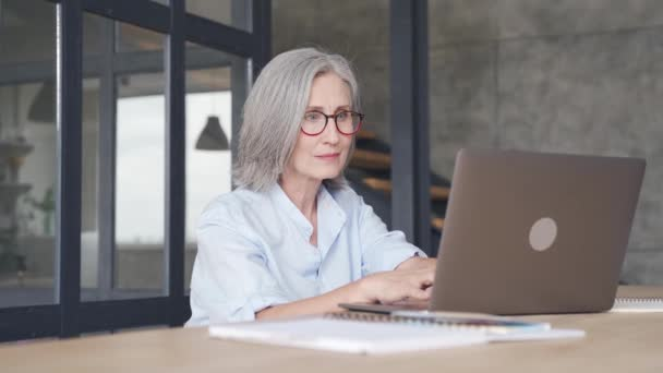 Usmívající se žena středního věku pomocí notebooku sedí na pracovišti.