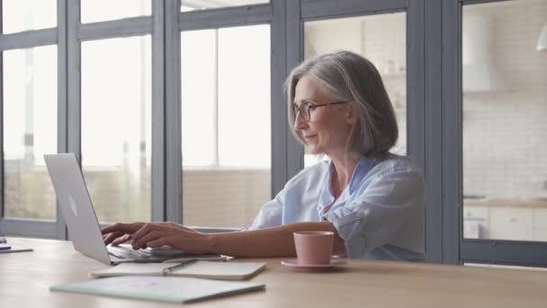 Idősebb érett középkorú nő laptoppal ül a munkahelyen.