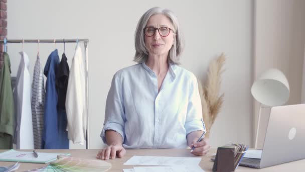 Glückliche Modedesignerin mittleren Alters am Arbeitsplatz, Porträt.