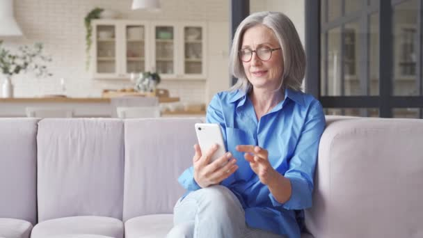 Nadšený starší žena vítěz čtení zprávy na smartphone doma.