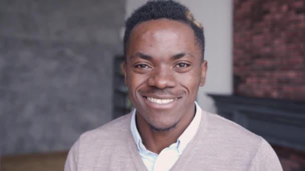 Mosolygó fiatal afrikai férfi néz kamera otthon, fejlövés portré.