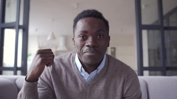 Glücklicher afrikanischer junger Mann spricht mit Blick auf Kameravideotelefonie zu Hause.