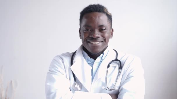 Glücklicher afrikanischer Arzt blickt auf Kamera an weißer Wand.