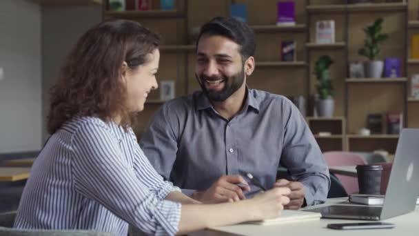 Dva šťastně přátelské rozmanité profesionální zaměstnanci, kteří diskutují v práci.