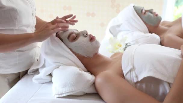 kosmetička pomocí prstu třít obličejovou masku na mladé asijské ženy čelo a kolem očí, vdo by handheld