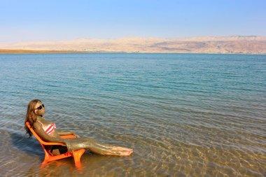 Girl smeared with therapeutic mud sunbathes, Dead Sea