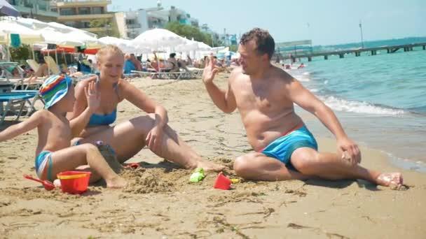 Famiglia di tre che dà hi-fives sulla spiaggia