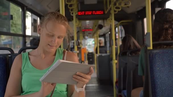 Happy pretty blonde with tablet PC riding in the bus