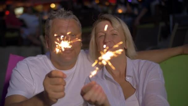 Starší pár s Bengálsko osvětlení venkovní v noci