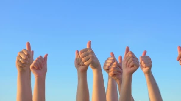 Hands up with thumbs-up against blue sky