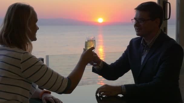 Paar zu rösten, mit Wein und Sonnenuntergang über Meer genießen