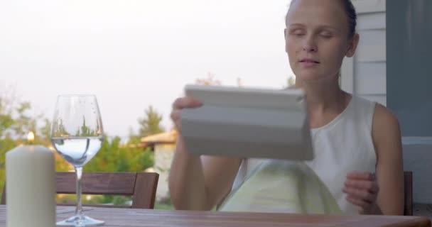 Žena pomocí podložky a pitnou vodu v venkovní terasa
