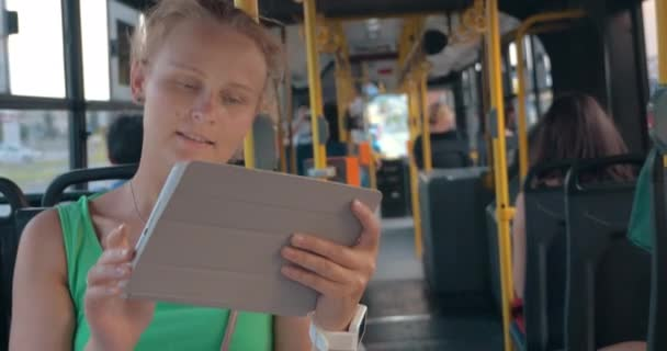 Smiling Woman with Tablet in Bus