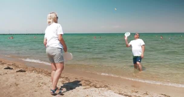 Uomo e donna che gioca volano sulla spiaggia