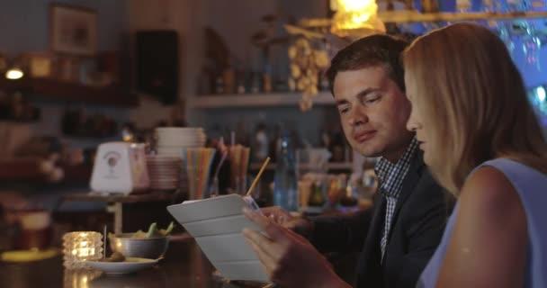 Muž a žena s touch pad v baru