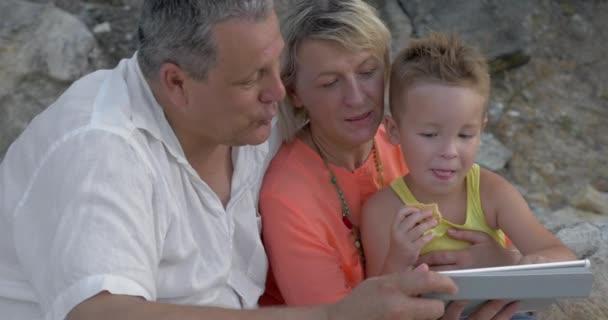 Child enjoying pad game with grandparents