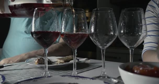 Man pouring red wine in four glasses
