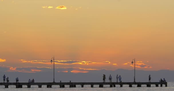 Cinemagraph - People enjoying seascape from the pier at sunset