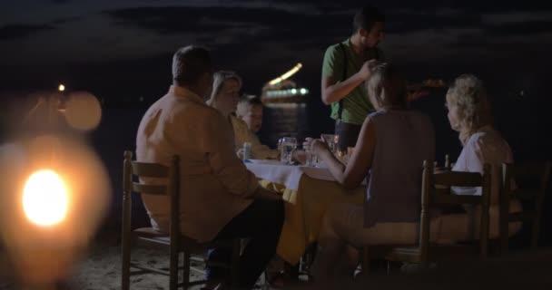Číšníku, sloužící večeři pro rodinu v venkovní kavárně