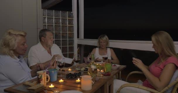 Rodina pomocí buněk a laptop během večeře