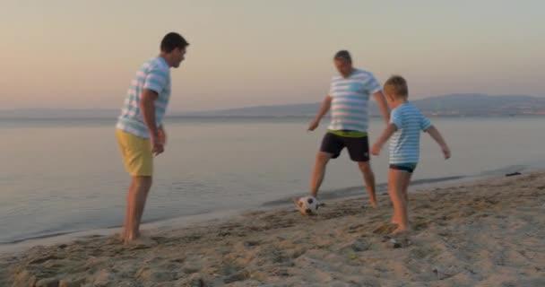 Muži ze tří generací hrát fotbal na pláži