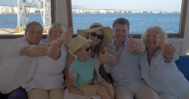 Familie an Bord des Schiffes zeigt Daumen hoch