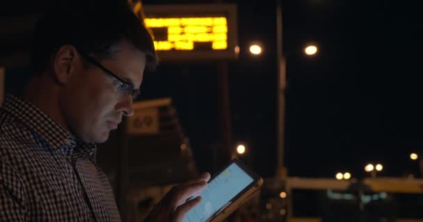 Man with tablet computer on bus station at night