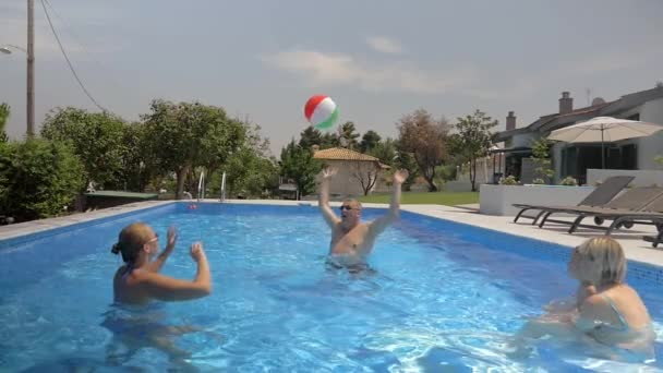 Family playing with a ball in the pool