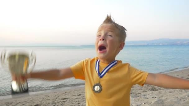 Malý chlapec vítěze medaile a pohár