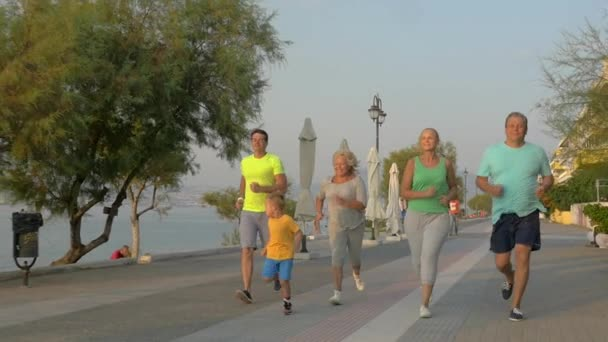 Big family running on road next to the sea