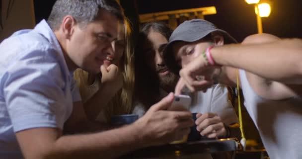 Přátelé na smartphone sledování a směje se na večírku