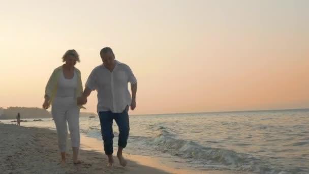 Starší pár, běžící na pláži při západu slunce