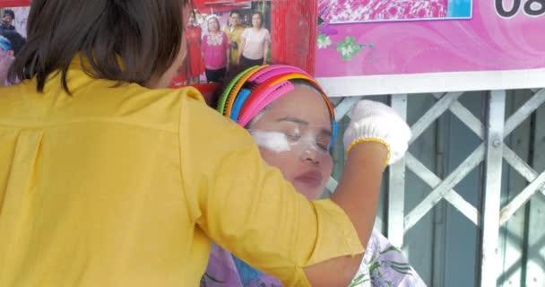 Service of eyebrow pluckering in the street. Bangkok, Thailand