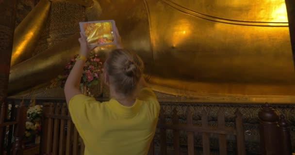 Turista a pad figyelembe fotót fekvő Buddha szobor Bangkokban