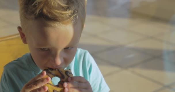 Boy eating chocolate donut and drinking water