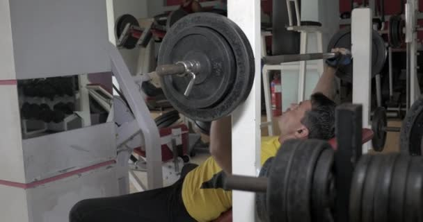 Sportsman flexing chest muscles on bench