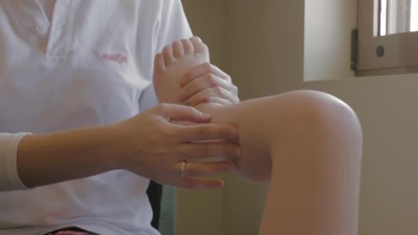 Terapeut dělat masáž nohou, dítě